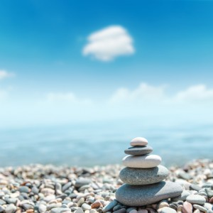 Spiritual Medium representedby pile of soul stones like zen near sea.